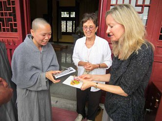 Annie giving American Indian gifts to nun at Lunhua Nunnery near Huangmei. This site is next to the Fourth Ancestor's Temple. Sensei Janet Ables of the Still Mind Zendo standing by.